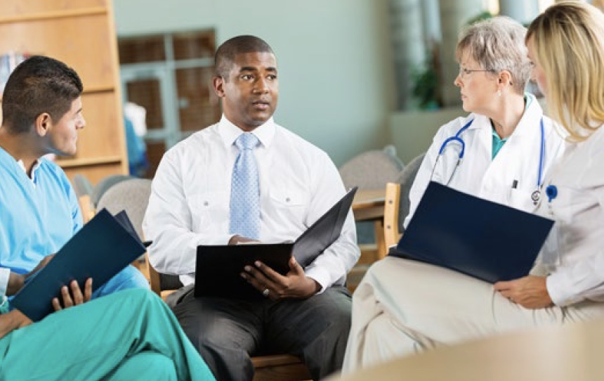 Healthcare professionals sitting in a circle discussing a case